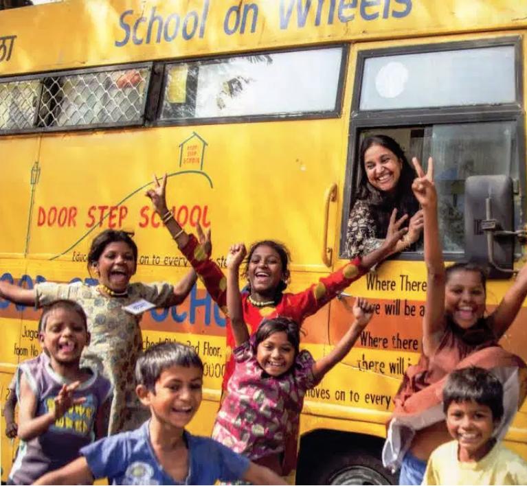 Bina ve öğrenciler, tekerlekli bir okul otobüsünün önünde poz veriyorlar